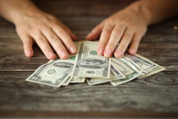 Man shpreading dollar bills on a wooden table.